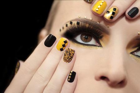 Manicura caviar en el esmalte de uñas de color amarillo y negro en la chica con las pestañas falsas y diamantes de imitación de diferentes formas.