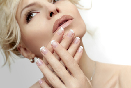 finger nail: Short French manicure on hands of a young woman.