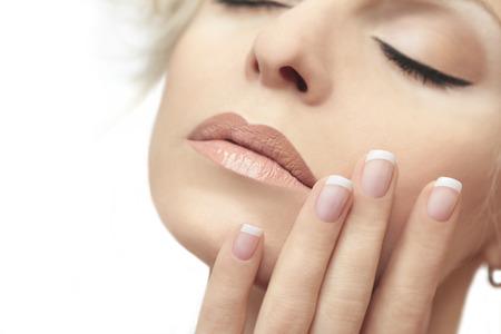 Korte Franse manicure op de handen van een jonge vrouw. Stockfoto