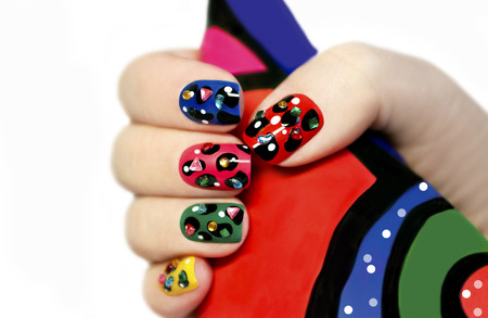 Colorful manicure on nails with colorful pattern and rhinestones on white background.