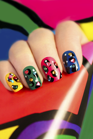 yellow art: Colorful manicure on nails with rhinestones and design points. Stock Photo