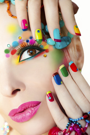 red nail colour: Colorful French manicure and makeup on the girl with rhinestones.