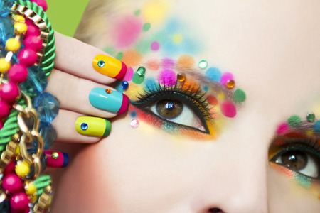 Kleurrijke Franse manicure en make-up op het meisje met strass.