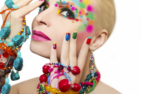 bead jewelry: Colorful makeup and manicure with ornaments of different shapes and colors on the blonde girl. Stock Photo