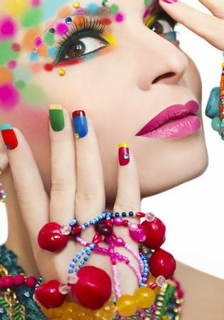 Kleurrijke make-up en manicure met ornamenten van verschillende vormen en kleuren op het blonde meisje.