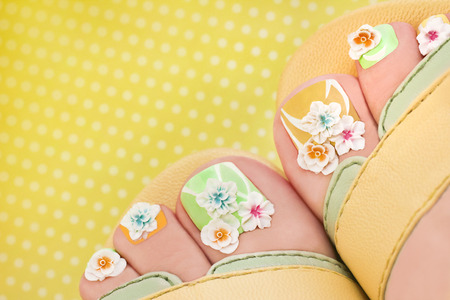 Summer flower pedicure with decorative flowers and different shades of lacquer on the womens feet.