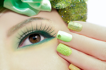 nail art: Green makeup and nail Polish with sparkles and rhinestones of different shapes.