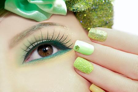 pesta�as postizas: Maquillaje verde y esmalte de u�as con destellos y pedrer�a de diferentes formas.