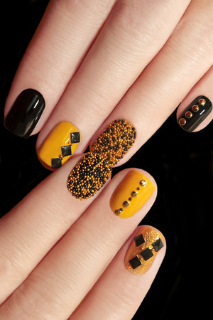 Kaviaar manicure in geel zwarte nagels met zwarte en gouden steentjes op een zwarte achtergrond.