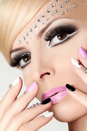 rhinestones: Fashion nails and makeup with rhinestones on nails and on the face of a woman with blond hair.