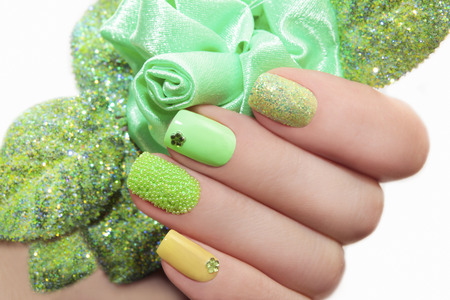 Manicure with green rose and a different design of sequins and rhinestones on nails.