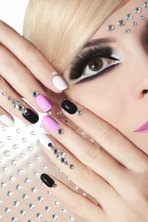 hair part: Fashion nails and makeup with rhinestones on nails and on the face of a woman with blond hair.