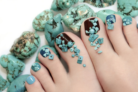 Pedicure with turquoise stones and jewelry made of turquoise on the women\