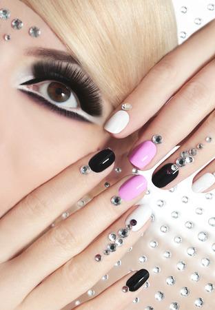 pesta�as postizas: Los clavos en la forma corta con diamantes de imitaci�n y lacas de colores sobre la chica con el pelo rubio y pesta�as postizas negras.