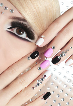 false eyelashes: The nails on the short form with rhinestones and colored lacquers on the girl with blond hair and black false eyelashes.