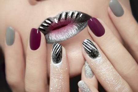Design with white and black stripes on the lips and nails with glitter.