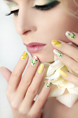 The makeup on the girl with the rose design on nails with roses. Archivio Fotografico
