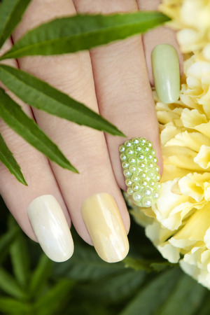 mother of pearl: Nail design with pearl rhinestone and multicolored mother of pearl lacquer on a woman39s hand.