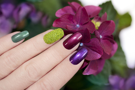 Nail designs with colored sand and dark pearlescent varnishes artificial nails.