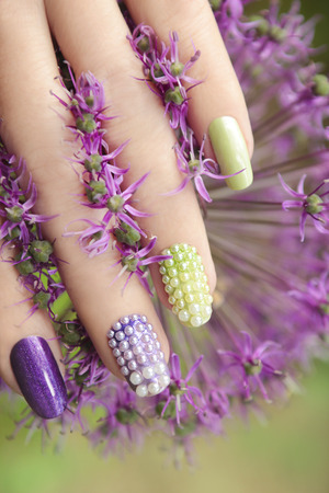 finger nail: Pearl nail design on colored nails with the flower.