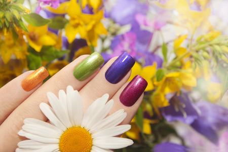 Kleurrijke gemanicuurde nagels vierkante vorm met bloemen. Stockfoto