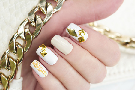 gold chain: Multi-color pastel manicures with gold metallic rhinestone and chain in his hand. Stock Photo