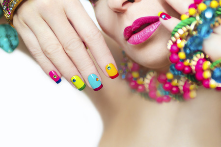 french model: Colorful French manicure with Rhinestones and ornament on the arm with the pink lips. Stock Photo