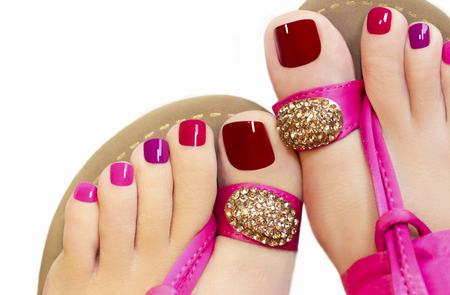 Pedicure with different colors of paint on a womans feet in pink sandals on a green background.