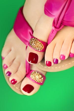 pedicura: Pedicura con diferentes colores de pintura en pies de una mujer en sandalias de color rosa sobre un fondo blanco. Foto de archivo