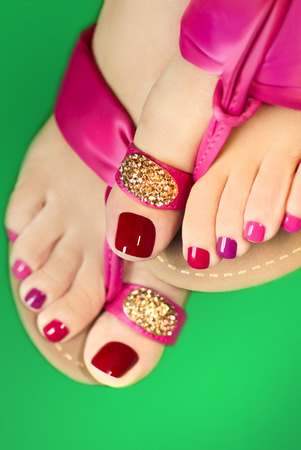 pedicura: Pedicure with different colors of paint on a womans feet in pink sandals on a white background.