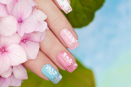 Pastel manicure with rhinestones and sequins on the background of Hydrangeas.