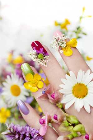 Nail design with flowers and colored lacquer on a womans hand.
