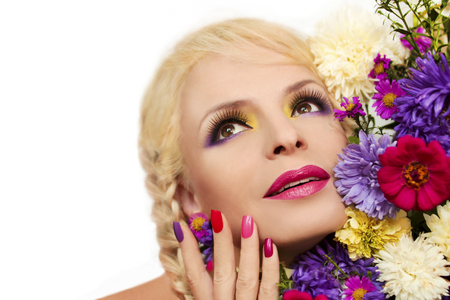 beauty face: Colorful makeup and manicure with summer flowers asters on a white background.
