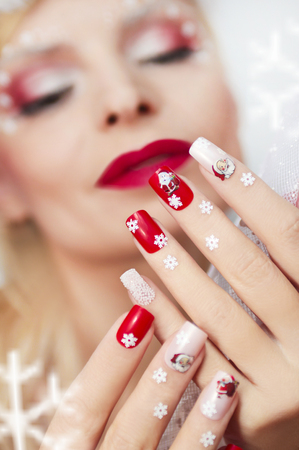 christmas manicure: Christmas manicure with Santa Claus and snowflakes on red and white nail Polish.
