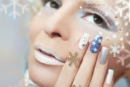 nail design: Snow manicure with silver nail Polish and snowflakes. Stock Photo
