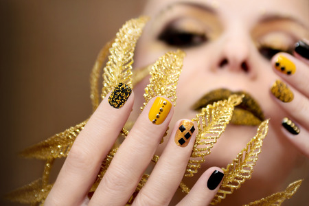 hand art: Yellow black manicure with metallic crystals of different shapes and colors on short nails. Stock Photo