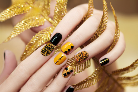 Yellow black manicure with metallic crystals of different shapes and colors on short nails. Stock Photo