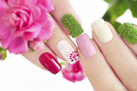 manicura: Manicura multicolor con patrón de flores, bolas verdes y un patrón de malla en las uñas. Foto de archivo
