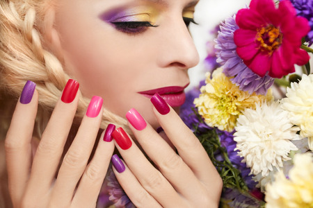 artificial model: Colorful makeup and manicure with summer flowers asters on a white background.