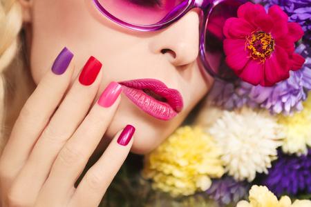 manicura: Colorida del maquillaje y la manicura con flores de verano áster. Foto de archivo