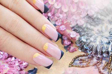 pink nail polish: Pastel pink manicure with black and gold nail Polish.