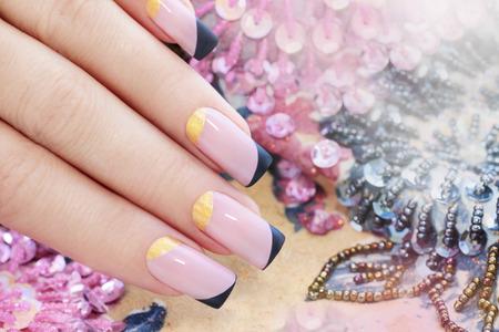 Pastel roze manicure met zwart en goud nagellak.