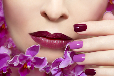 Pink maroon manicure on a young woman with orchids. Stock Photo