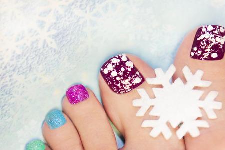 pedicura: manicura de invierno con copos de nieve y las lentejuelas de diferentes colores.