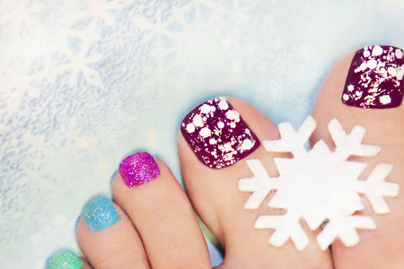 pedicure: Winter manicure with snowflakes and sequins of different colors.