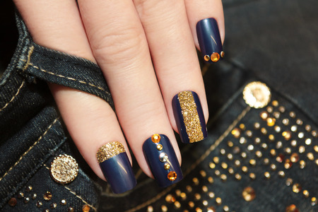 artificial nails: Denim blue manicure with rhinestones and sequins. Stock Photo