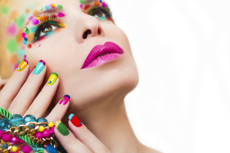 Colorful makeup and manicure with ornaments of different shapes and colors on the girl. Stock Photo
