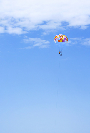 colourful sky: The couple ride in the sky on colourful parachute over the sea in summer.