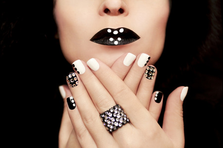 christmas manicure: Multicolored manicure with white and black nail Polish decorated with rhinestones and a ring on his hand. Stock Photo
