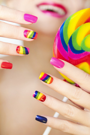 artificial nails: Rainbow manicure on artificial nails square shape, with a Lollipop in his hand. Stock Photo